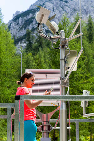 Pretty woman meteorologist reading meteodata instruments in modern meteorologic observation station, high in mountains 版權商用圖片 - 83564393