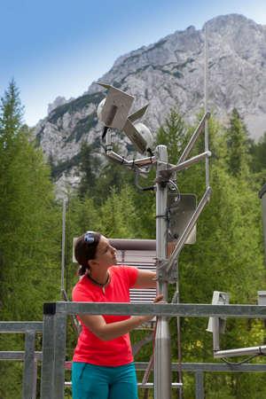 예쁜 여자 기상 현대 meteorologic 관측소에서 meteodata 악기를 읽고, 산속에 높은