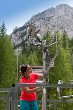 Bastante mujer meteorólogo leyendo meteodata instrumentos en la moderna estación de observación meteorológica, alto en las montañas