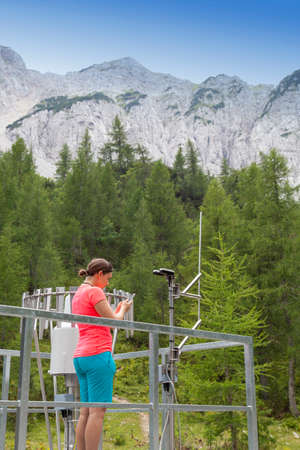 hygrometer: Pretty woman meteorologist reading meteodata instruments in modern meteorologic observation station, high in mountains
