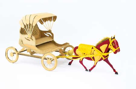 Vue latérale d'un cheval décoré en carton tirant un chariot en carton sur fond blanc