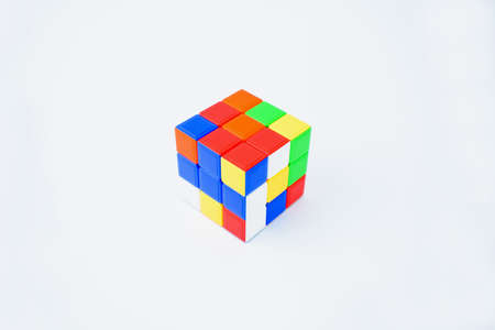 A scrambled Rubik cube is isolated on a white background displaying different color