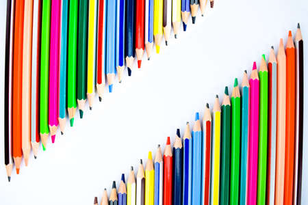 Similar row of different colored pencil crayons facing each other on a white paper ,making a space to write different text Standard-Bild - 139599714