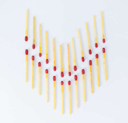 An arrow shape made of two rows of red match sticks on a white background