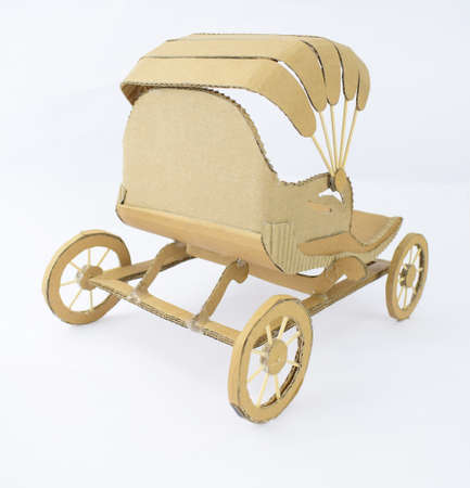 Back view of a brown colored carriage made of recycled card-board displayed on an isolated white background
