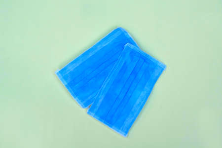 Two blue surgical mask with rubber straps isolated on a light blue background
