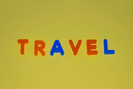 Travel word written with different colored letter blocks arranged on a yellow background Stock fotó