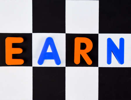 Earn word written with different colored letter blocks arranged on a black and white background
