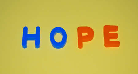 Hope word written with different colored letter blocks arranged on a yellow background Stock fotó