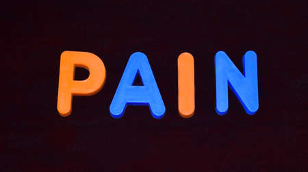 Pain word written with different colored letter blocks arranged on a dark background