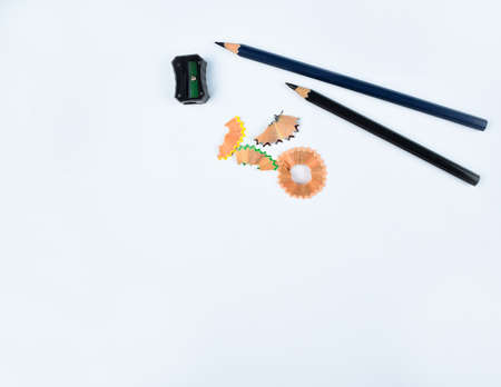 Two black wood pencil,a black pencil sharpener and some pencil shavings scattered on a white background