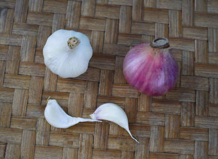 photograph of couple of onion and garlic with their buds scattered beside them on a wood color background