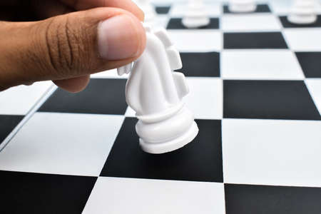One person moving a placed white knight from a black square of the chess board