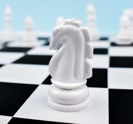White knight placed on top of a white square of the chess board in a chess game Stock Photo