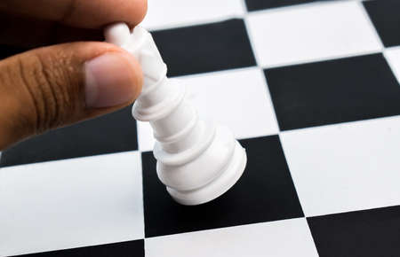 A person moving the mighty white queen from a black square of the chess board