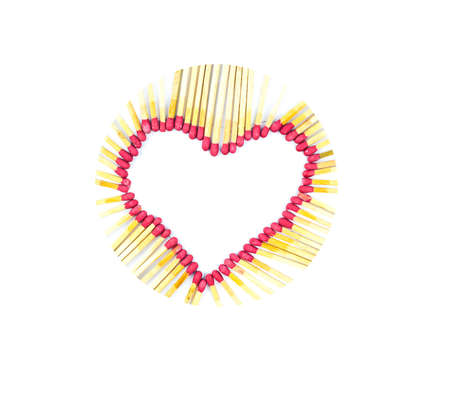 Circled heart made with burned red colored match sticks in front of a white isolated background