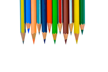 Line of different colored wood pencil crayons placed before a white isolated background