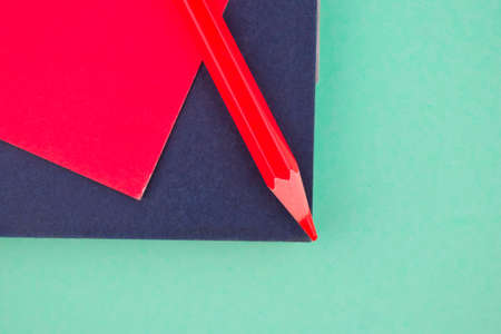 red colored wood pencil crayon placed on a red sticky note on a black note paper diary