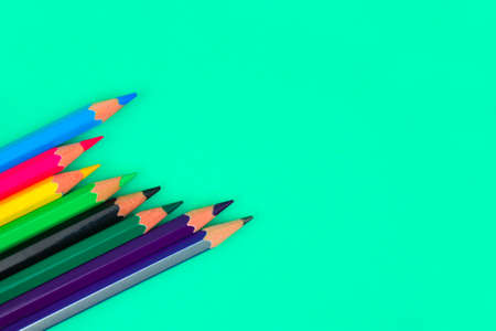 Few different color wood pencil crayons placed on top of a light blue paper background