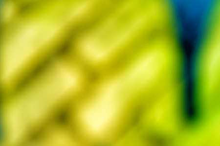 Abstract bright blurry un-focused background pattern texture with bricks running diagonally in green white turquoise and with a blue stripe on the right side.