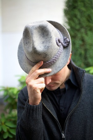 caucasian man in bow position with fingers holding hat