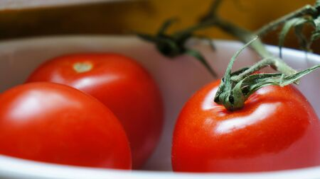 Three small red tomatoes in a white bowl. One tomato even carrying the green stalk. Stock Photo