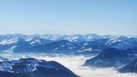 Snow-covered mountains above the clouds in a winter atmosphere