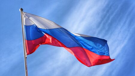 adverse: Flag of Russia. Russian Flag on flagpole waving unfavorable due to windy conditions in front of blue sky.