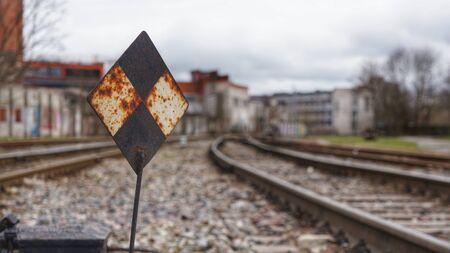 Railroad Sign in Shape of Rhombus between Railway Tracks Stock Photo