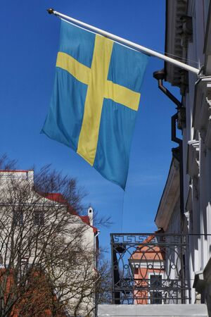 Flag of Sweden waving above the balcony of a building, blue sky behind.