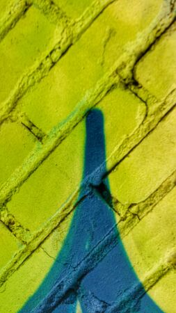 Abstract bright blurry un-focused background pattern texture with bricks running diagonally in green yellow turquoise and with a painting looking similar to the Eiffel tower.