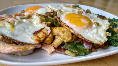 Delicious healthy meal with fried eggs, mushrooms, salmon fish and vegetables on white plate.
