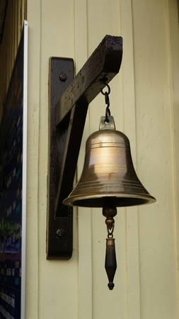 Bronze Bell hanging on wooden dark hook at bright wooden wall. Photo taken at a train station in Thailand.