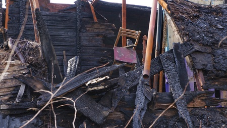 felony: Remains of a burned down house. Old chair hanging above burned boards, planks and other wooden material of a house.