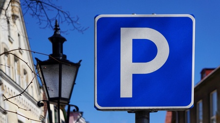 Street Sign Parking Zone in front of old historic buildings and the blue sky. Besides an old street lamp. Stock Photo