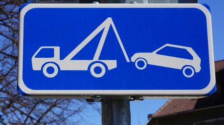 Street Sign of Tow Away Zone in front of buildings Stock Photo