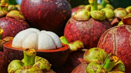 Mangosteens Bunch of fruits, ripe mangosteen fruit halved with pulp visible.