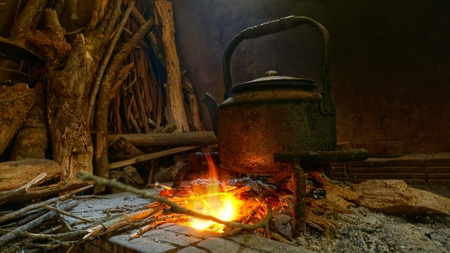 Native image pot of water on burning fire.