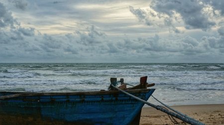 tied down: Old wooden boat lying on beach, tied down with rope. Ocean with splashing waves and cloudy sky in the background. Stock Photo