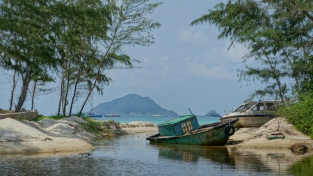 con dao: Boat in lagoon. An old obsolete blue boat laying on the beach shore of a lagoon. Tropical scene looking like paradise taken on the Vietnamese island Con Dao.