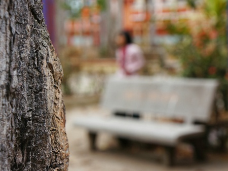 Blurred unfocused grey bench and unidentifiable woman behind focused tree trunk