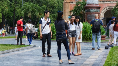 Ho-Chi-Minh-City (former Saigon), Vietnam, 22nd July 2016. Unidentified young people taking photos of each other in parkin front of statue. Editorial