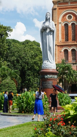 Ho-Chi-Minh-City (former Saigon), Vietnam, 22nd July 2016. Two unidentified young women taking photos of each other in front of a statue at the Notre-Dame-Cathedral. Two other woman looking to the flowers in front of the statue. Editorial