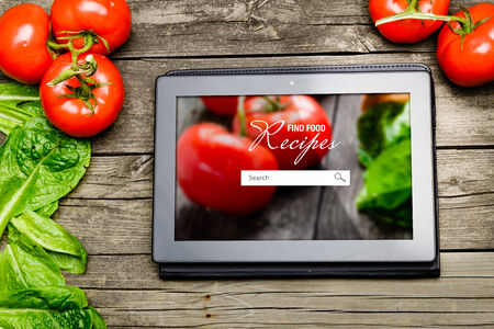 Online Cooking recipes on tablet pc with vegetables on backround. photo