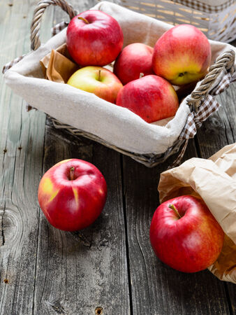 Apples in basket on old grey wood table photo