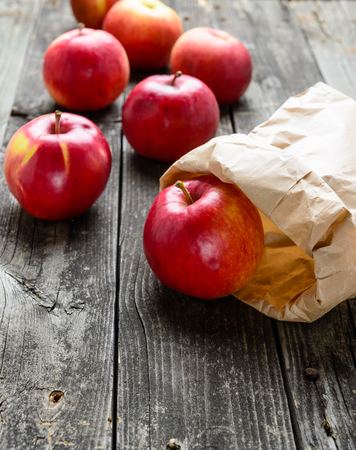 apple paper bag: Apples on old grey wood table. Brown paper bag Stock Photo