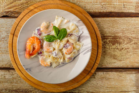 Farfalle pasta with shrimps in a creamy sauce on a gray plate on a wooden table on a round stand. Horizontal photo