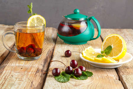 black tea in a glass cup with mint cherries and lemon on a wooden table next to fresh cherries and a teapot.