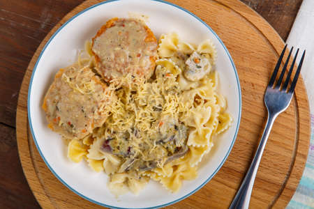 Pasta in a creamy sauce with mushrooms and chicken meatballs in a beige plate on a wooden table Horizontal photo. Stock fotó