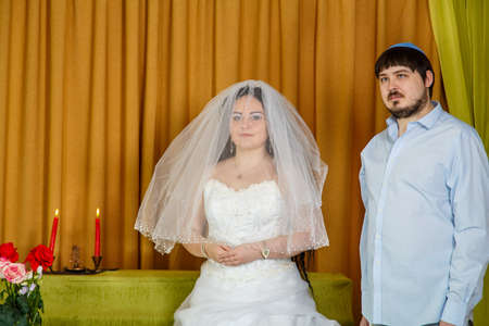 A Jewish bride with a veiled face of the Badeken tradition and a groom in a synagogue stand in front of Chupa during a ceremony.
